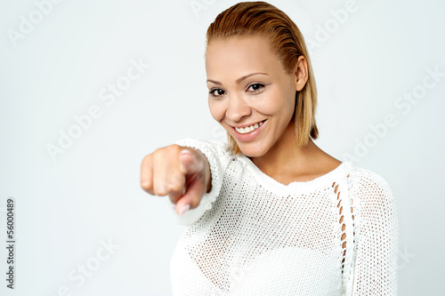 Cheerful young lady pointing you out