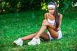 injured sportswoman sitting on the grass