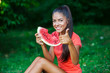 young beautiful brunette woman eating watermelon