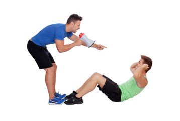Personal trainer with a megaphone and boy making abdominal