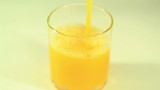 Orange juice flows in a glass