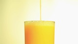 Bright orange juice flowing in a glass close up