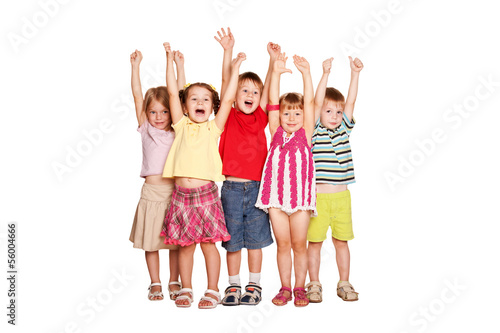 Group of little children raising hands up and smiling