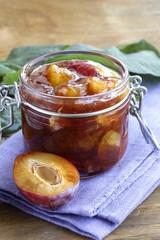 Plum jam in  jar on  wooden table