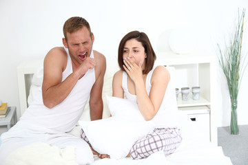 Tired young couple yawning in bed