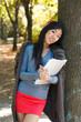 Joy girl with notebook near tree