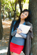 Cute girl with notebook near tree