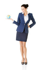 Young businesswoman holding globe