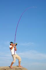 Pêcheur en surf casting combattant un poisson