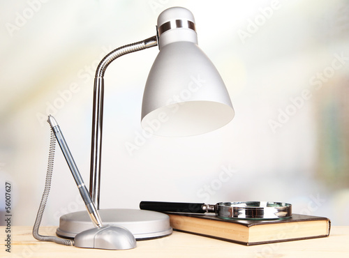 Table lamp and book on desk in room
