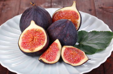 Ripe figs on plate wooden table close-up