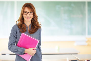 Smiling teacher standing in classroom
