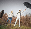 Woman and man with umbrellas during strong storm wind