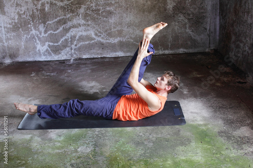 man on mat practicing pilates