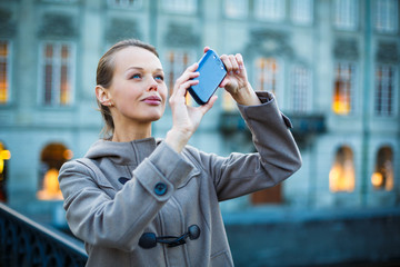 Elegant, young woman taking a photo with her cell phone camera