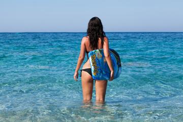 Frau mit Surfbrett steht im türkisblauen Meer