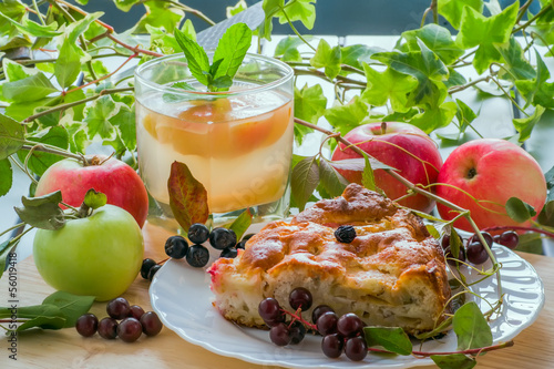 Slice of tasty homemade pie with apples and glass of compote
