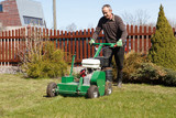Man working with Lawn Aerator poster
