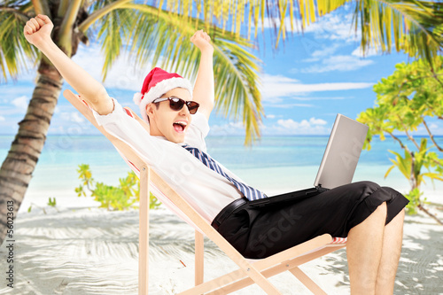 Excited male with santa hat working on a laptop, on a beach