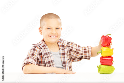 Little smiling boy holding colorful peppers on a table