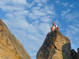 Man sitting on top of a mounain