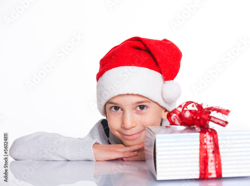 Little boy in Santa's hat with gift box