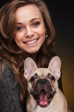 Portrait of beautiful girl with french bulldog puppy