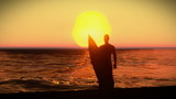 Silhouette of a surfer with his surfboard on the sunset