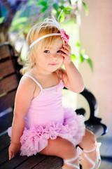 Cute baby ballerina in a beautiful summer garden