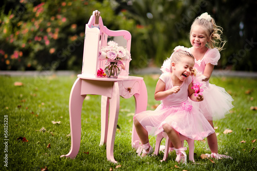 two happy little girl wearing in princess cotumes have a fun in