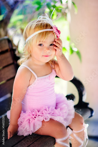 Cute baby ballerina in a beautiful summer garden