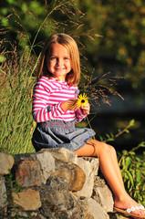 happy little girl holding a flower
