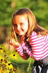 little girl smelling a flower