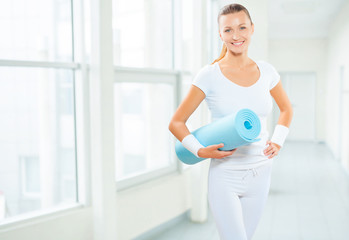 a female wearing white sports clothes holding blue yoga mat