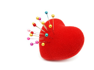 Red heart stabbed by pins on white background