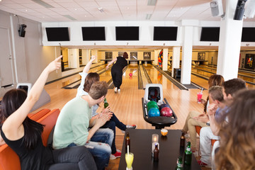 Friends Cheering Woman Bowling in Club