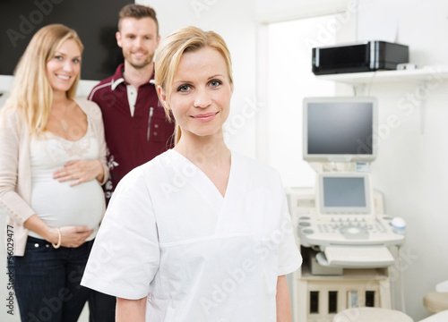 Confident Doctor With Expectant Couple In Background