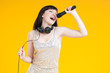 Young caucasian woman singing with microphone, yellow background