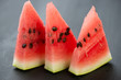 Three slices of ripe watermelon on dark wooden background