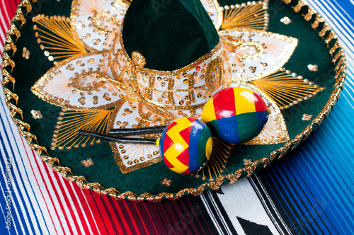 Mexican sombrero and maracas on a striped poncho