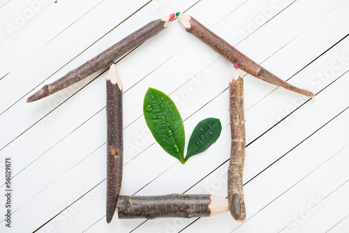 Ecohouse made up of wooden pencils and green leaves
