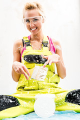 Female construction worker with can of paint and paint brush