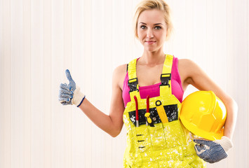 Woman in coverall holding hard hat and showing thumbs up