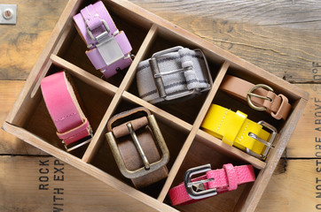 Set of vintage belts in wooden crate on rusted wooden background