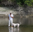 Owner and his dogs play in shallow water