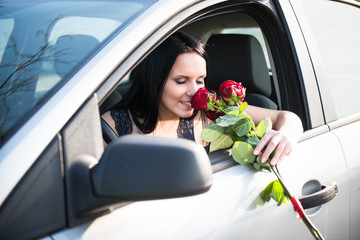 Woman with roses in car