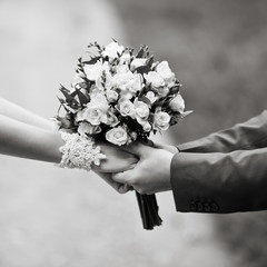 hands of a weddingl couple in black and white
