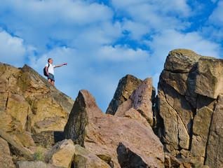 Man on top of a rocky mountain cliff