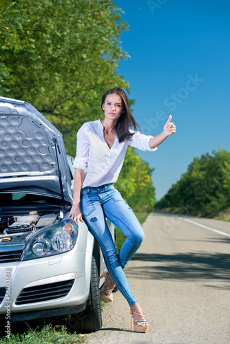 Beautiful woman hitchhiking by a broken car