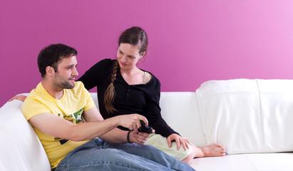 Junges, gutaussehendes Paar spielt Videospiel auf dem Sofa